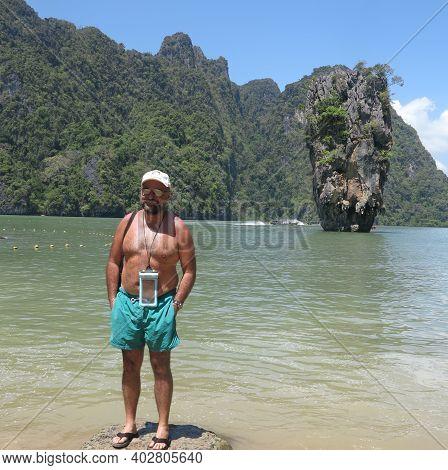 Male Tourist Traveler Relaxing And Posing On James Bond Island, Phuket, Thailand. Amazing Nature Sea
