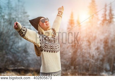 Outdoor close up portrait of young beautiful woman with long hair wearing hat, sweater posing in nature view. Christmas, winter holidays concept. Snowfall. Snow trees on background.