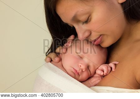 Young mother of mixed race posing with her 7 days old newborn baby in closeup