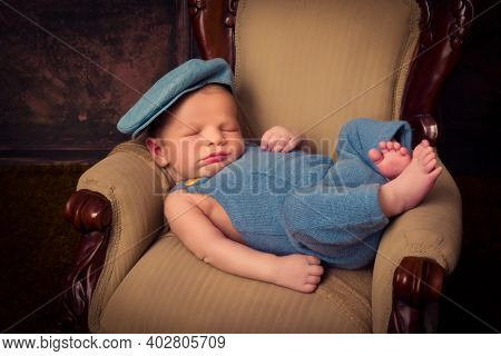 Newborn baby of 7 days old sleeping on an antique French armchair