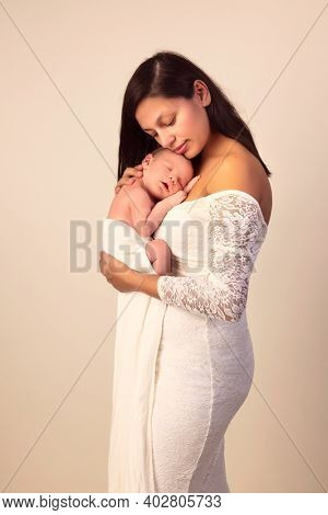 Beautiful young mother in a white lace gown posing with her 7 days old newborn son