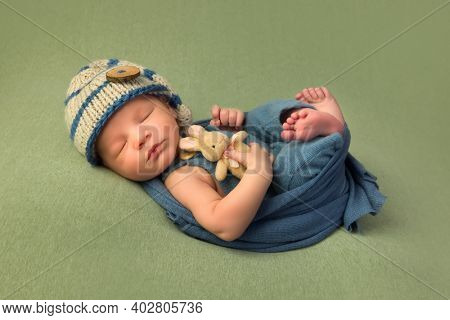 7 days old newborn baby sleeping on a soft green blanket