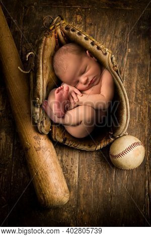 Newborn baby sleeping in an old leather baseball glove
