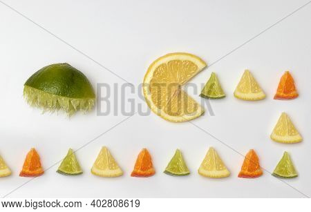Lemon Eats Pieces Hunted By Lime. Pac Man Minimal Citrus Fruit Flat Lay Concept Showing Spring Summe