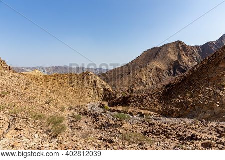 Hajar Mountains Landscape In Hatta, United Arab Emirates, Seen From A Hiking Trail, With Harsh Clima