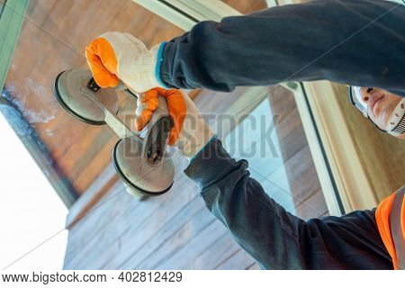 Construction Workers Installing A Window In A New Building,hand Holding A Special Tool For Carrying