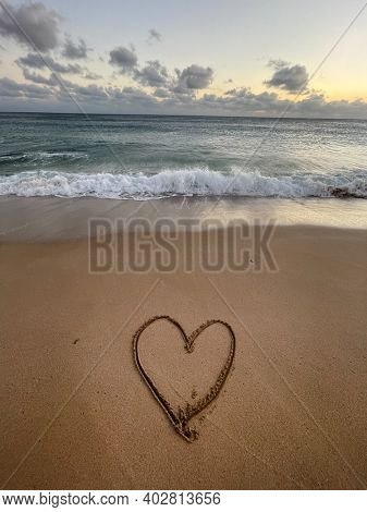 Heart is drawn on the sand. Beautiful view on the waves