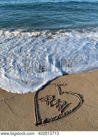 Heart ,2021is drawn on the sand. Beautiful view on the waves