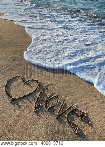love is drawn on the sand. Beautiful view on the waves