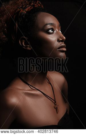 Side view of beautiful african christian woman stands on black background and looks to the spotlight. Her brow skin illuminated in light.