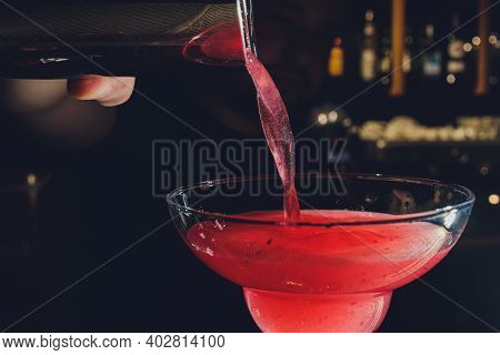 Close Up Details Of Barman Pouring Vodka Cosmopolitan Cocktail In Martini Glass.