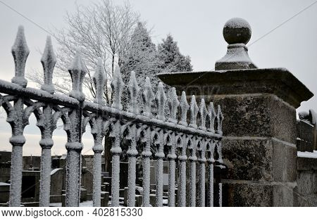Black Cemetery Gate Made Of Heavy Cast Metal. The Lattice Is In The Shape Of Spears. A Column Of Gra