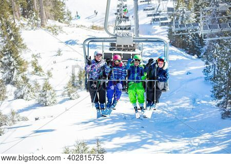 Children In Bright Ski Outfit Wave Hands Sitting On The Chairlift Happy Lifting On The Mountain