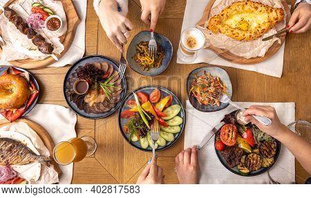 Dining Table With Various Dishes Top View, Group Of People Dining Together. People Use Cutlery.