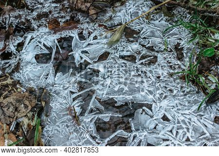 Abstract Winter Background, Cracked Ice On Frozen Puddle. Ice Fragments On Frozen Water. The Ice Bro