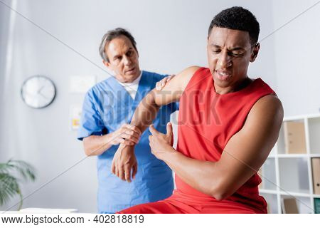 Mature Chiropractor Working With Injured African American Man In Sportswear
