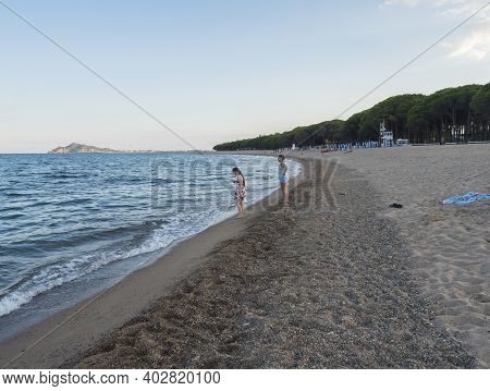 Santa Maria Navarrese, Sardinia, Italy, September 6, 2020: Two Young Woman Standing On The Sand Beac
