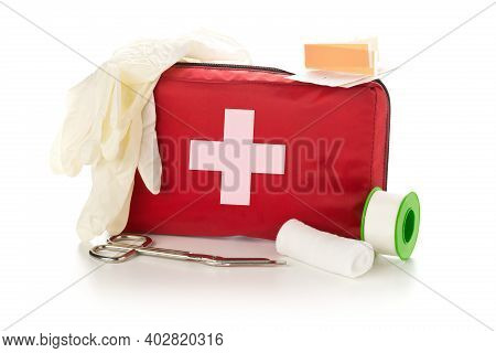 Red First Aid Medical Kit Bag With Scissors, Tape And Gloves Standing Over White Background