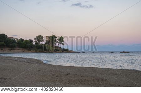 View Of Empty Spiaggia Di Santa Maria Navarrese Sand Beach With Green Trees And Old Stone Tower Torr