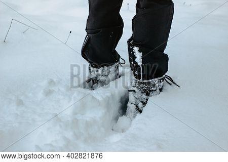 Detail Of Warm Waterproof Boots In Deep Fresh Snow.female Feet In Black Shoes, Winter Walking In Sno