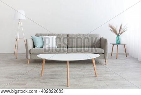 Minimalist Living Room Interior. White Table, Modern Sofa With White And Blue Pillows, Lamp And Vase