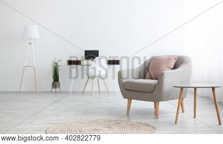 Modern Workspace At Home For Remote Work. Simple Armchair With Pink Pillow, Next To Little Table And