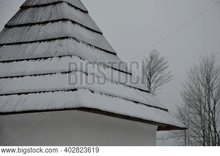 Shingled Wooden Roof On A Building In The Mountains. Snow And Icing Covered In Chipped Shingles. Bro