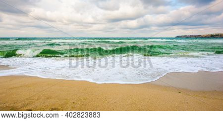 Sea Tide On A Cloudy Sunset. Green Waves Crashing Golden Sandy Beach. Storm Weather Approaching. Sum