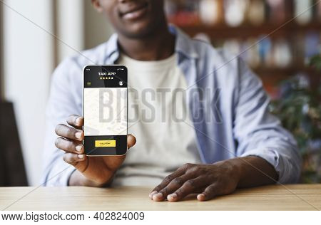 Black Man Holding Smartphone With Opened Taxi Services Mobile App On Screen, African American Guy Sh
