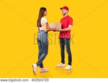 Delivery Courier Guy Giving Parcel Box To Woman Standing Over Yellow Studio Background. Post Package