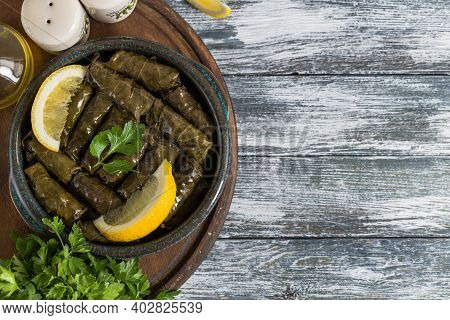 Dolma - Stuffed Greek Wine Leaves (dolmades) On A Blue Wooden Background