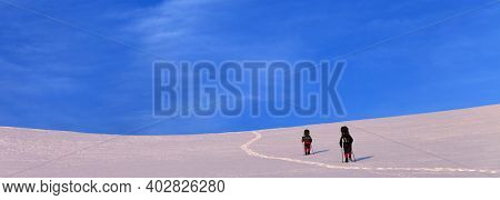 Two Hikers On Sunrise Snowy Plateau In High Mountains. Turkey, Central Taurus Mountains, Aladaglar (