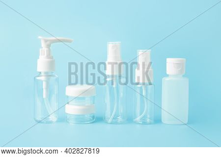 Travel Toiletries Beauty Kit Set On Blue Background. Airplane Approved Luggage Bottle Container Size