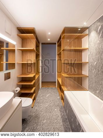 Modern home interior with white walls and hardwood floors. Modern bathroom with wood and stone, minimalist. Nobody inside