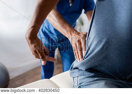 Cropped View Of Mature Chiropractor Working With African American Patient