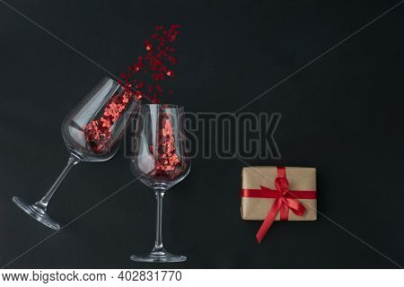 Two Wine Glasses With Little Red Heart Sparkling Confetti And Wrapped Giftbox On Black Background, L