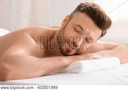 Relaxed Middle Aged Man Attending Spa Salon On Weekend, Lying On His Belly On Massage Table, Closeup