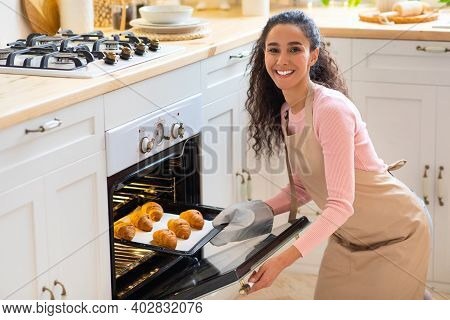 Happy Young Woman Taking Out Tray With Fresh Baked Croissants From Oven In Kitchen, Smiling Lady Enj