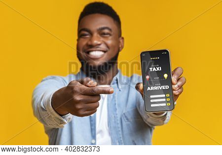 Joyful Black Guy Pointing At Smartphone With Opened App For Taxi Rate, Cheerful African Man Enjoying