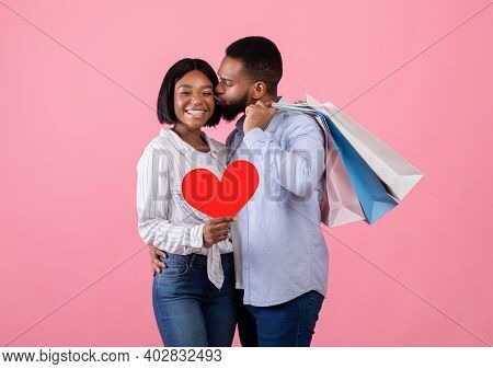 Passionate Black Man Holding Shopping Bags, Kissing His Girlfriend With Red Heart On Pink Studio Bac