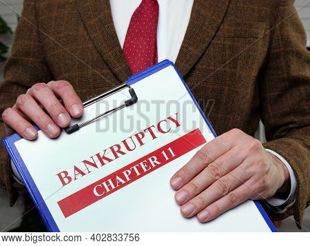 Documents About Bankruptcy Chapter 11. Man Holds Papers.