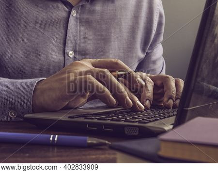 Blogger Writes Text In A Laptop. The Man Is Typing On The Keyboard.