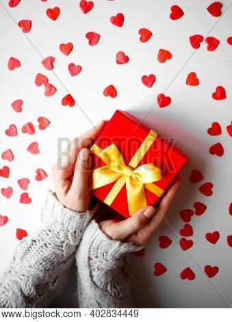 Hands Hold A Gift On A White Background With Red Hearts