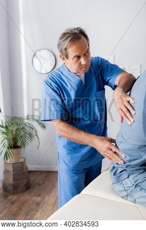 Mature Chiropractor Working With African American Patient On Massage Table