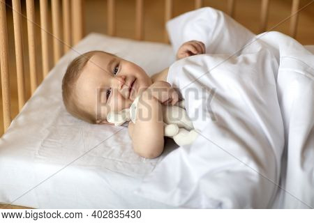 Adorable Smiling Blonde Baby Laying In Wooden Crib Under Blanket. Happy Little Kid Infant Woke Up Af