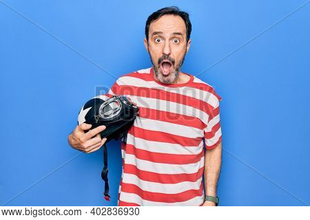 Middle age handsome motorcyclist man holding moto helmet over isolated blue background scared and amazed with open mouth for surprise, disbelief face