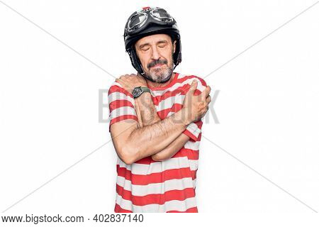 Middle age handsome motorcyclist man wearing moto helmet over isolated white background hugging oneself happy and positive, smiling confident. Self love and self care