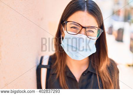 Young beautiful brunette woman wearing medical mask and glasses. Standing at town street leaning on the wall
