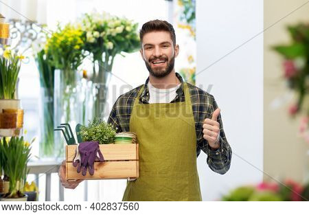 gardening, farming and people concept - happy smiling male gardener in apron with box of garden tools showing thumbs up over flower shop background