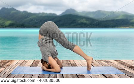 fitness, sport, people and healthy lifestyle concept - woman making yoga in headstand pose on mat over ocean and mountains in french polynesia on background